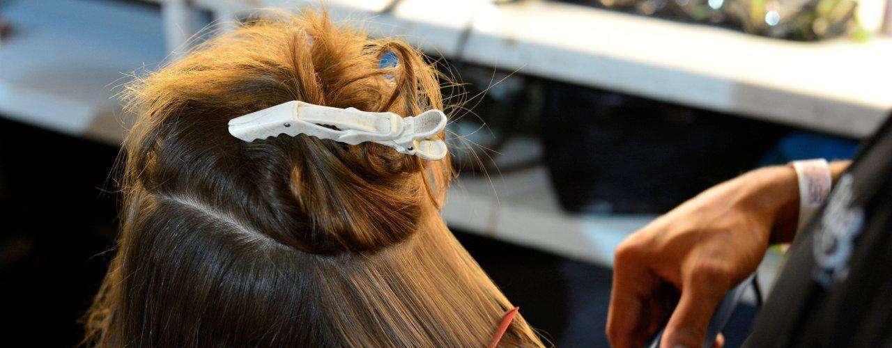 Antes de prender o coque, os cabeleireiros alisaram os cabelos das modelos