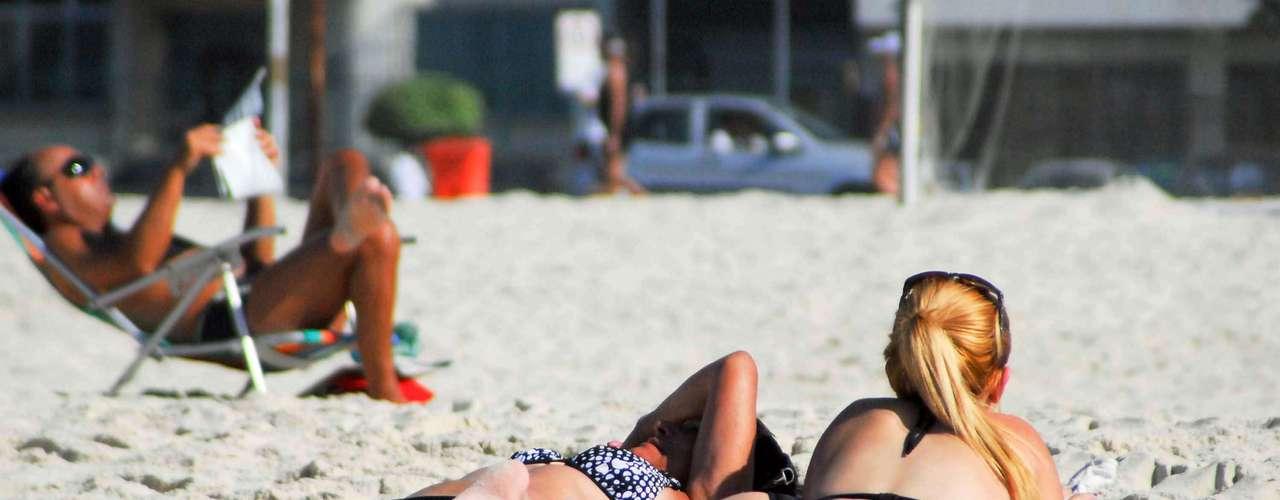 29 de abril Mulheres tomam banho de sol na praia de Copacabana