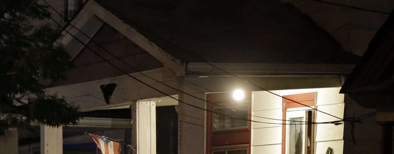 Agentes do FBI recolhem evidências da casa durante a noite