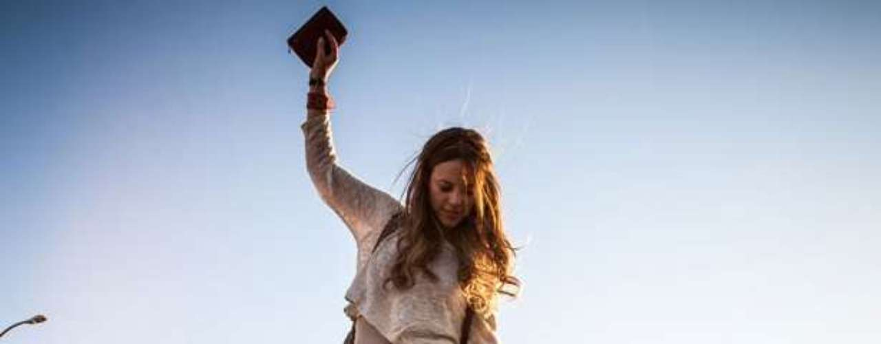 Paloma usa blusa solta e curta sobre outra justa, junto com saião em tie-dye e bota cano curto, em sua fase hippie