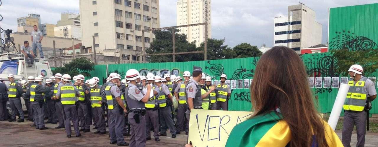17 de junho - Abraçada a bandeira do Brasil, jovem mostra cartaz a policiais militares que monitoram a movimentação no Largo da Batata