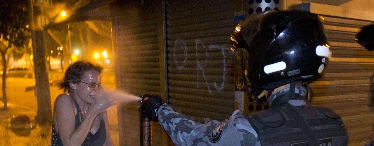 17 de junho- Policial militar joga gás de pimenta no rosto de uma mulher durante o protesto no Rio de Janeiro