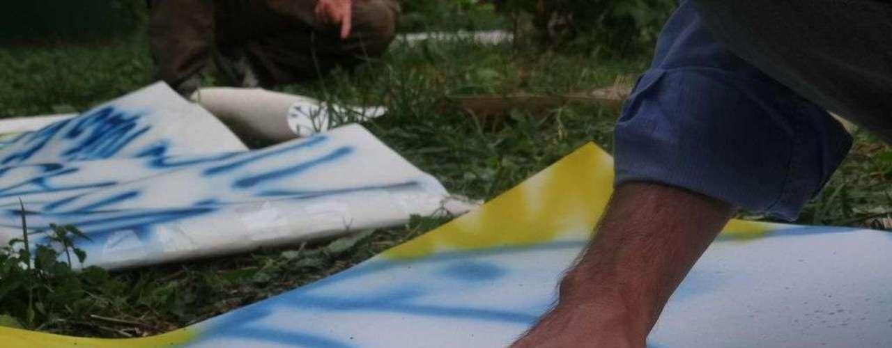 18 de junho - Com os dedos, jovem pinta cartaz para participar do protesto