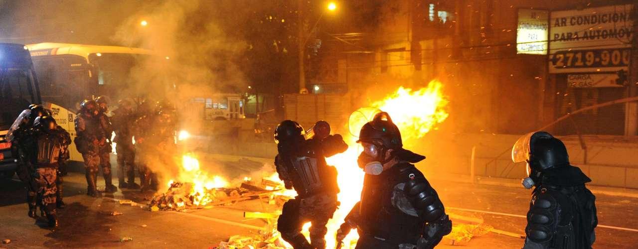 19 de junho -Policiais tentam extinguir fogo em barricada montada pelos manifestantes em Niterói