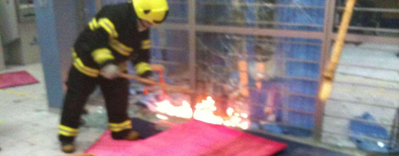 20 de junho Bombeiro apaga fogo colocado por vândalos em uma agência de um banco em Porto Alegre