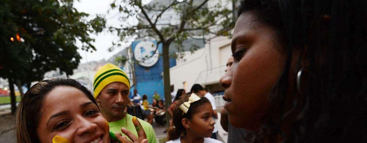 25 de junho - Jovem tem o rosto pintado nas cores da bandeira nacional no Rio