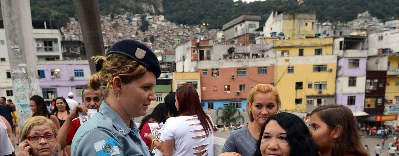 25 de junho - Policial distribui panfletos a manifestantes na favela da Rocinha, no Rio