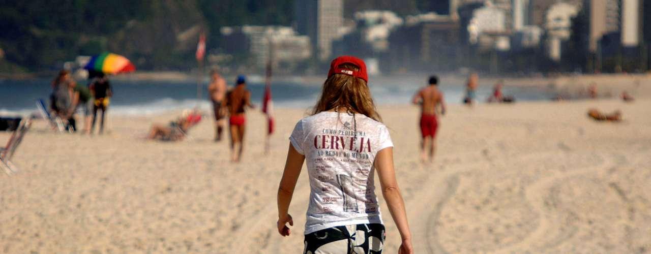 4 de julho Jovem aproveita calor no Rio para caminhar pelas areias de Ipanema