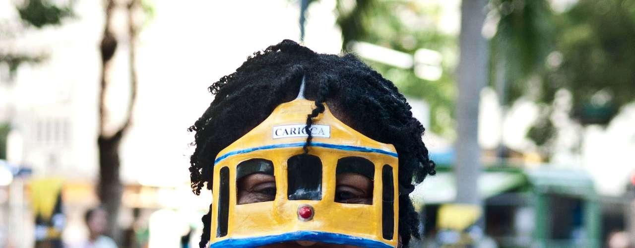13 de julho - Manifestante usa máscara em forma de bonde durante protesto no Rio