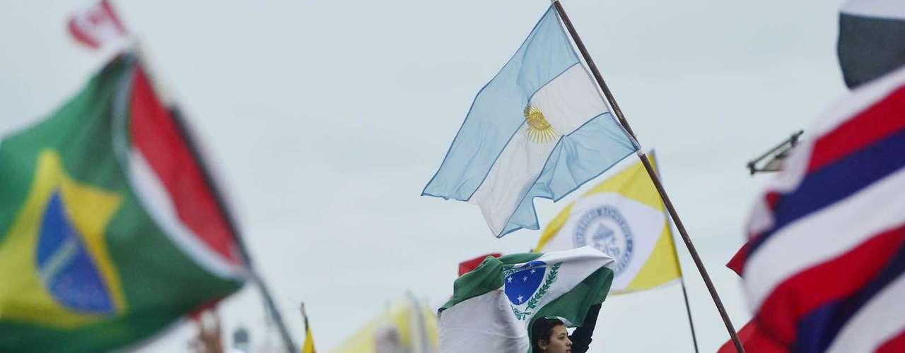 23 de julho -Fiéis levantam bandeiras na praia de Copacabana, enquanto aguardam missa de abertura da Jornada Mundial da Juventude