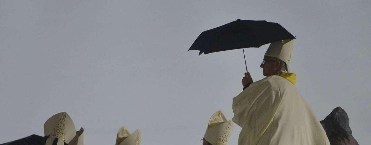 23 de julho -Religioso se protege da chuva durante a missa de abertura da Jornada Mundial da Juventude, em Copacabana