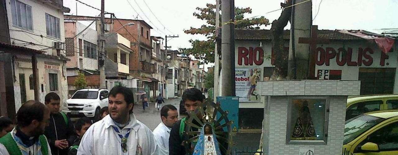 24 de julho - Empunhando com orgulho a bandeira de seu país, o grupo participou de uma procissão pelas ruas da favela de Manguinhos