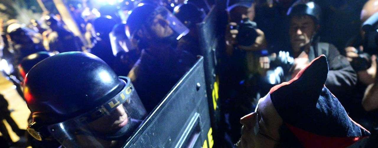 30 de julho - Manifestante encara policial