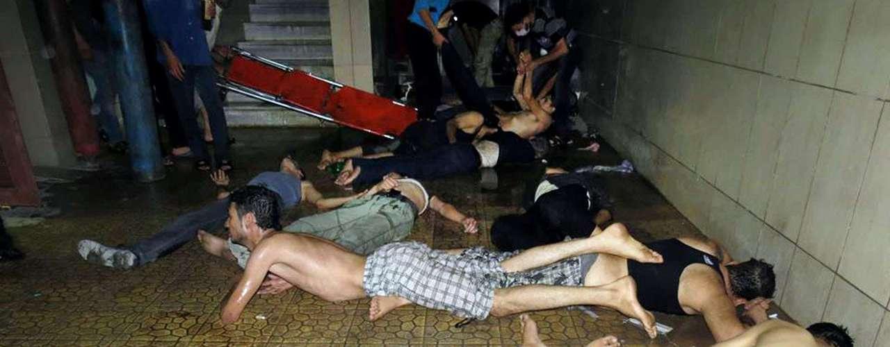 Homens esperam por atendimento após o suposto ataque químico das forças de segurança da Síria na cidade de Douma, na periferia de Damasco; a fotografia é do escrtitório de comunicação de Douma