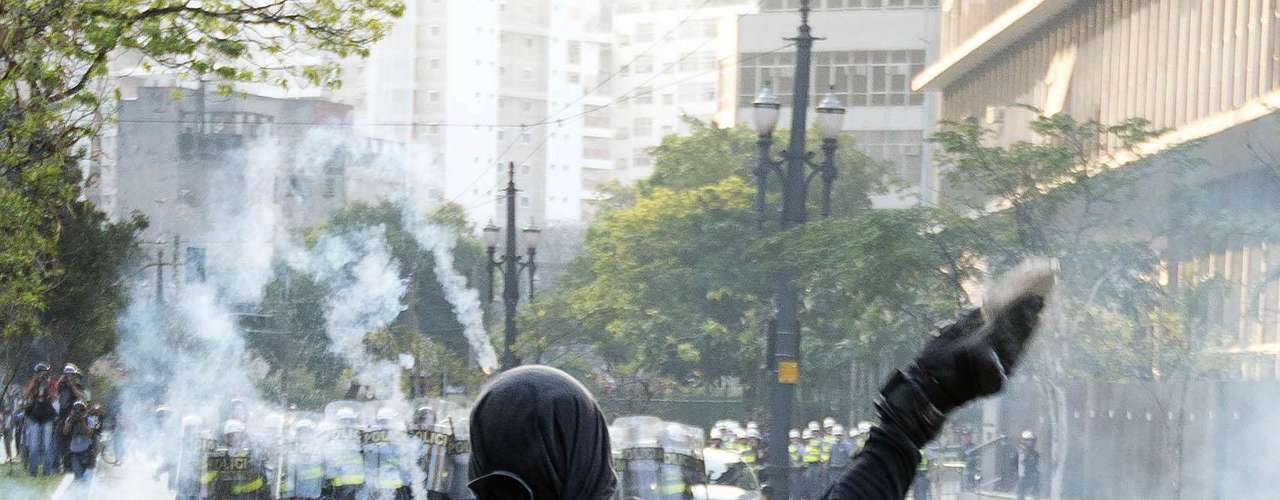 São Paulo - Manifestante joga pedra contra os policiais durante confronto na capital paulista