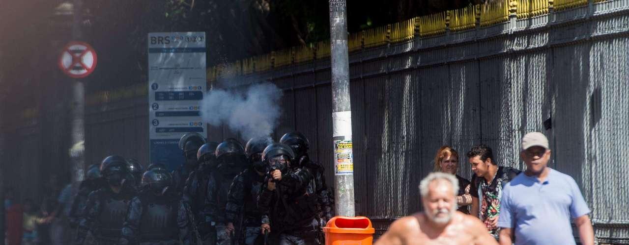 Rio de Janeiro - Homem caminha em meio ao confronto de manifestantes e Tropa de Choque do Rio