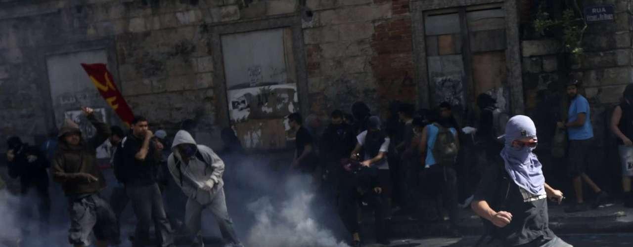 Rio de Janeiro -  Manifestante chuta bomba de gás lacrimogêneo na direção de policiais