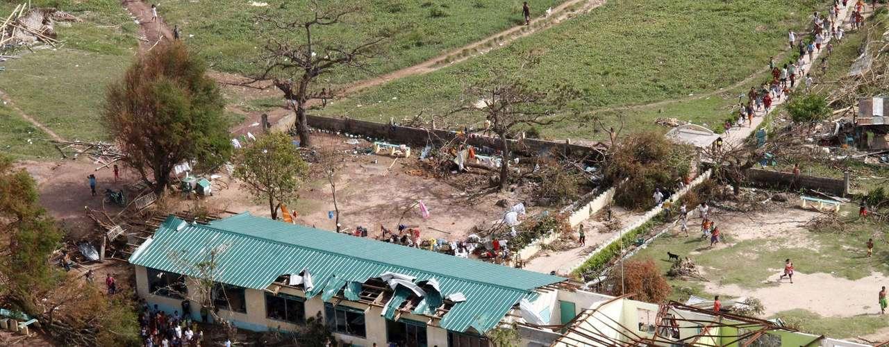 11 de novembro -Moradores correm na direção de helicóptero militar para pegar ajuda humanitária na província de Iloilo