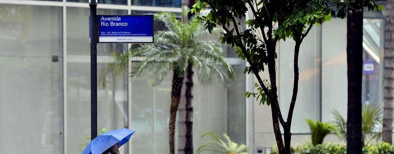 12 de novembro - Pedestre se abriga em guarda-chuva na avenida Rio Branco, no centro do Rio