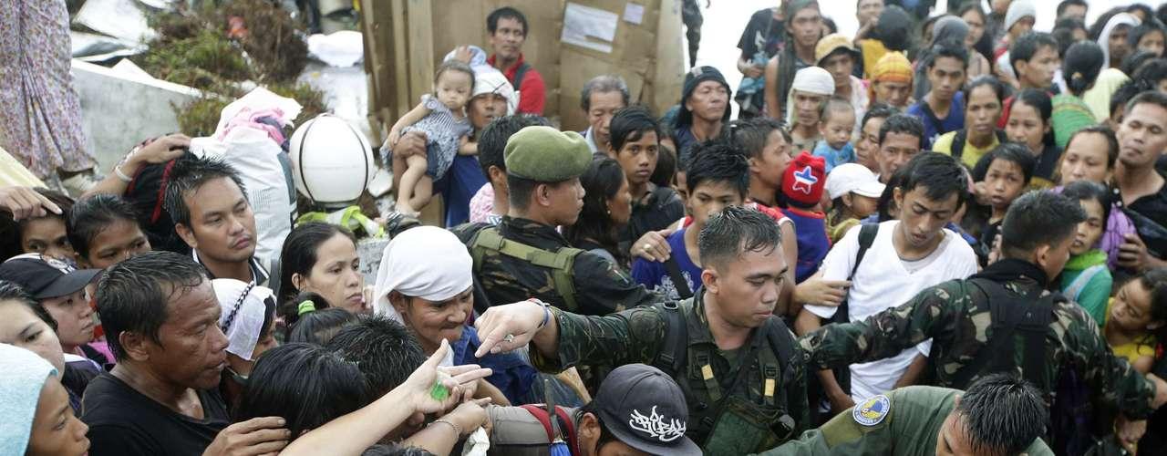 12 de novembro - Soldados tentam conter pessoas desesperadas para tentar embarcar no aeroporto deTacloban para deixar a cidade