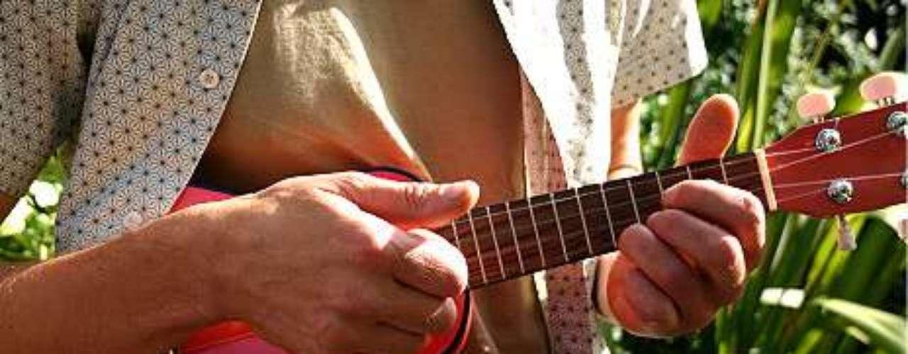 Jovem toca ukulele, um instrumento semelhante ao cavaquinho. Oadolescente americano descobriu ter talento para tocar 13 instrumentos musicais ao se recuperar de pancadas na cabeça.