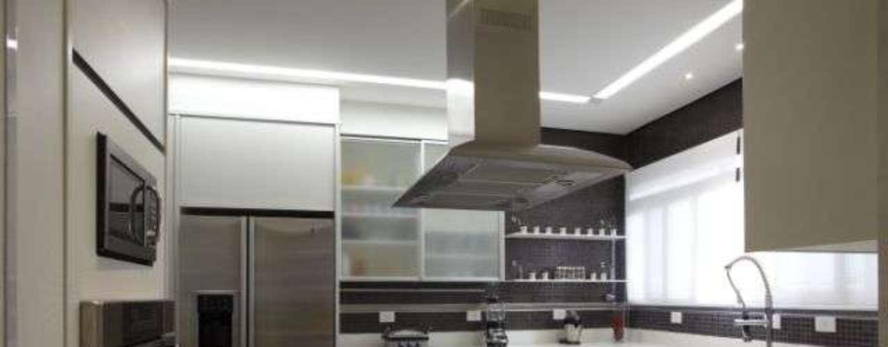 A arquiteta Adriana Bijarra Cuoco utilizou pastilhas que imitam inox na parede ao lado da geladeira e na parede da janela. O destaque fica por conta do cooktop na bancada no centro da cozinha. Informações: (11)5092-4057
