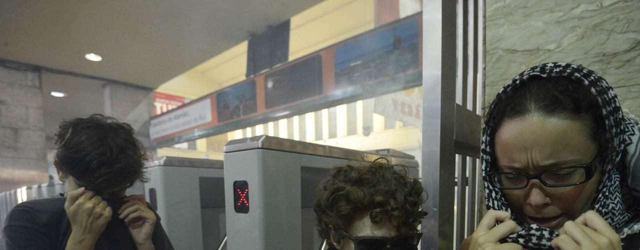 6 de fevereiro - Passageiros se protegem dentro da estação Central do Brasil, onde era forte o cheiro de gás lacrimogêneo