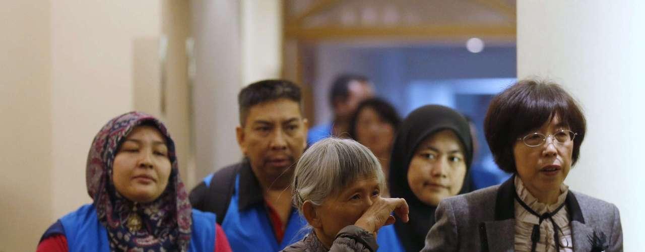 27 de março -Voluntários vestem coletes azuis e levam um parente para a sala de reuniões com o governo da malásia para atualização de informações sobre destroços que estão sendo procurados no Oceano Índico
