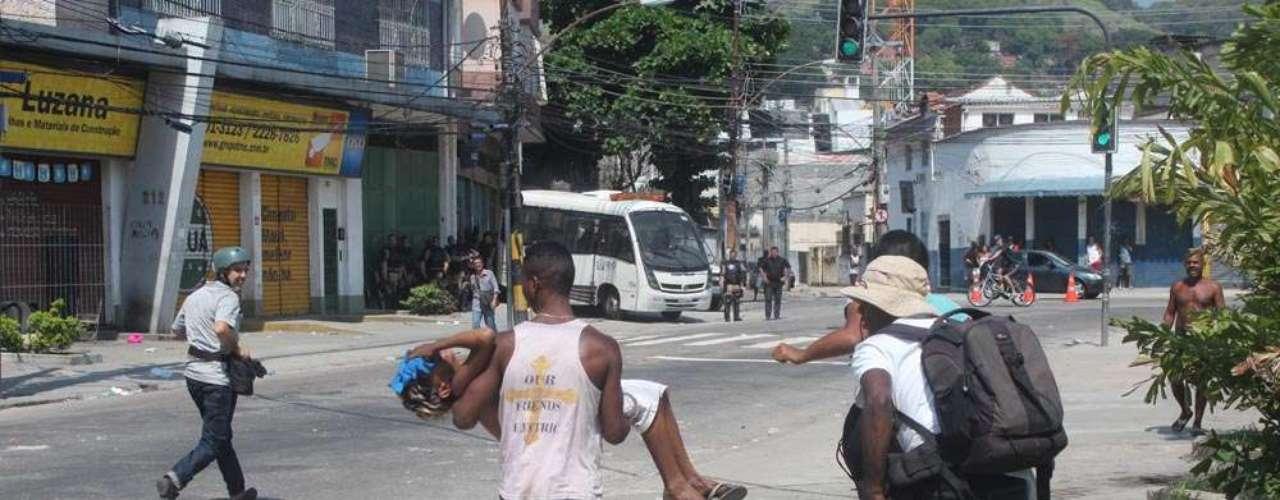 Menino vítima do gás atirado por PMs é carregado por moradores na favela do Rato Molhado