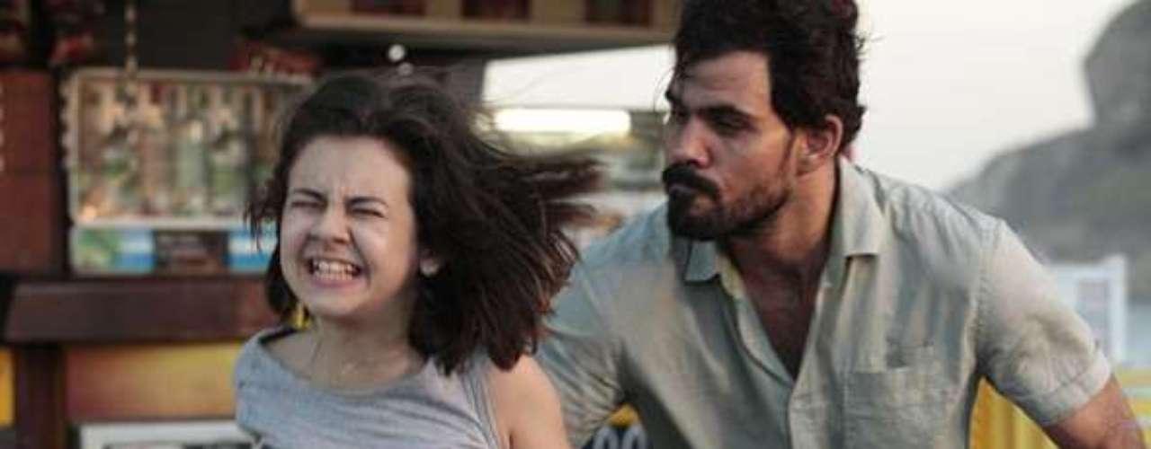 Paulinha (Klara Castanho) tenta correr e pedir ajuda na praia, mas é pega por Ninho (Juliano Cazarré)