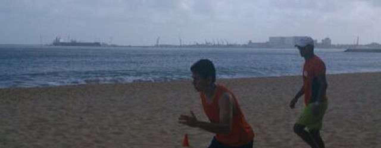 São-paulino Osvaldo treina na praia durante as férias