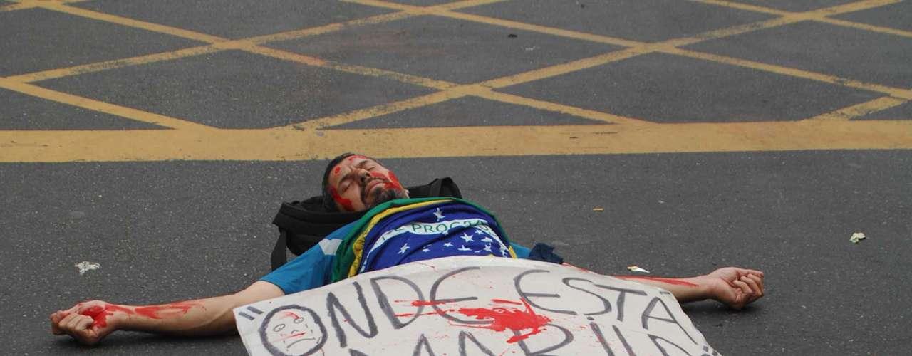 15 de agosto -  Manifestante deita na avenida Rio Branco para protestar contra o sumiço do pedreiro Amarildo