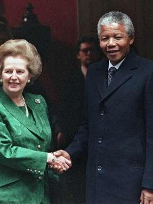 Após recusar inicialmente o encontro, Mandela pousou com Thatcher, sua detratora, em Londres, em 1990 Foto: AFP