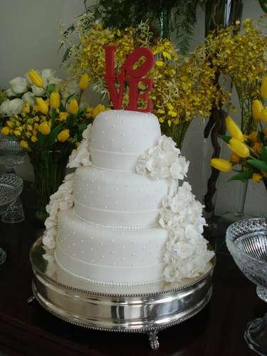 Bolo redondo branco de três andares coberto com pasta americana e detalhes de flores laterais, Simone Amaral - Sugar and Arts.Preço:R$ 200 o quilo de andar verdadeiro, andares falsos e flores são cobrados a parte