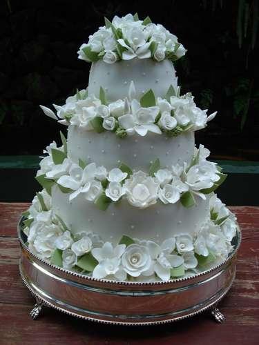 Bolo redondo branco de três andares coberto com pasta americana com flores grandes, Simone Amaral - Sugar and Arts.Preço:R$ 200 o quilo de andar verdadeiro, andares falsos e flores são cobrados a parte