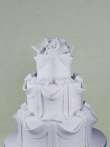 Bolo de três andares coberto de pasta americana com guirlandas, laços e rosas de açúcar no topo, Cake Design. Preço: a partir de R$ 1.000