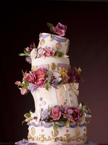 Bolo inclinado de quatro andares de banana com gianduia e capuccino coberto de pasta de açúcar e decorado com flores, The King Cake. Preço: a partir de R$ 180 o quilo