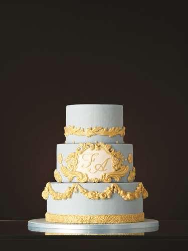 Bolo redondo de três andares de genoise branca com frutas vermelhas coberto com pasta de açúcar azul e decorado com detalhes em amarelo e iniciais dos noivos, The King Cake.Preço:a partir de R$ 180 o quilo