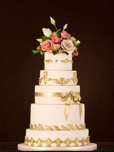Bolo redondo de cinco andares de maçã e champanhe coberto de pasta de açúcar branca decorado com flores, fita e detalhes em dourado , The King Cake.Preço:a partir de R$ 180 o quilo