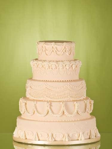 Bolo redondo de cinco andares de massa de amêndoas com geleia de damasco coberto com pasta de açúcar e com decoração imitando renda, The King Cake.Preço:a partir de R$ 180 o quilo
