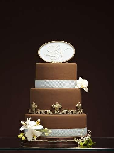 Bolo redondo de três andares de coco com trufa de maracuja e cocadinha coberto de pasta de açúcar marron decorado com flores, fitas e inicial dos noivos , The King Cake.Preço:a partir de R$ 180 o quilo
