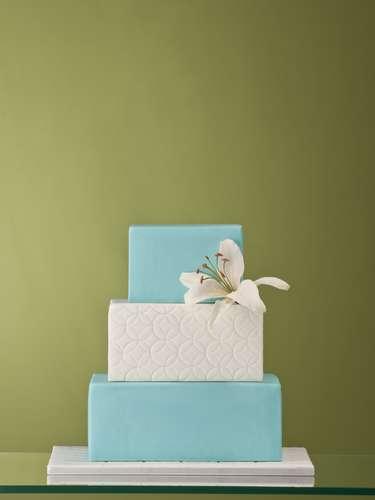 Bolo quadrado de três andares com trufa e contreau coberto de pasta de açúcar branca e azul decorado com trabalho imitando renda e flor , The King Cake.Preço:a partir de R$ 180 o quilo
