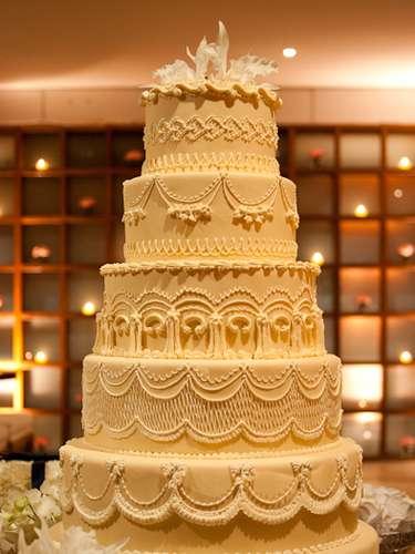 Bolo redondo de seis andares marfim coberto de pasta americana e decorado com trabalho em glacê e enfeite de flor natural no topo, Wayne Ferreira.Preço:R$ 140 o quilo