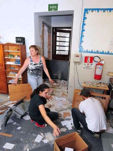 Funcionários tentam arrumar sala de fábrica após ação de assaltantes