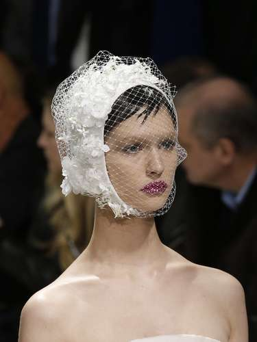 Modelo desfilou com arranjo na cabeça composto com renda sobre o rosto. Modelo foi criado pela Dior