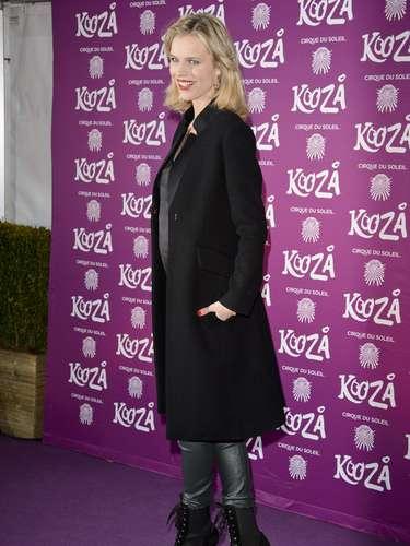 A modelo Eva Herzigova usa calça de couro skinny com botas e sobretudo, em visual todo preto