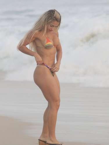 Ex- miss Bumbum, Priscila Freitas ajustou a parte de baixo do biquíni colorido antes de pegar um bronze