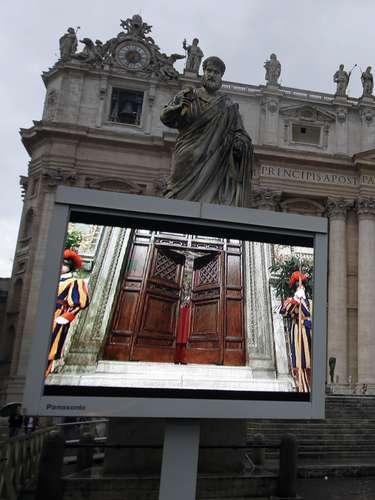 12 de março - Telão na Praça São Pedro mostra o momento em que as portas da Capela Sistina são fechadas para início do conclave