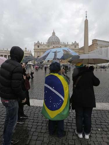 12 de março - Enrolada na bandeira do Brasil, mulher acompanha fiéis na Praça São Pedro, no Vaticano, onde cardeais se reúnem a partir de hoje para escolher quem será o próximo papa