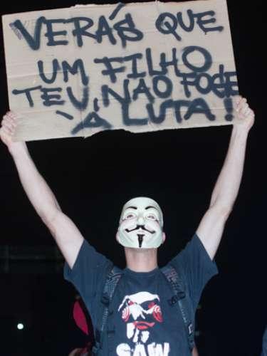 13 de junho - Mascarado, manifestante protesta e levanta cartaz comtrecho do hino nacional